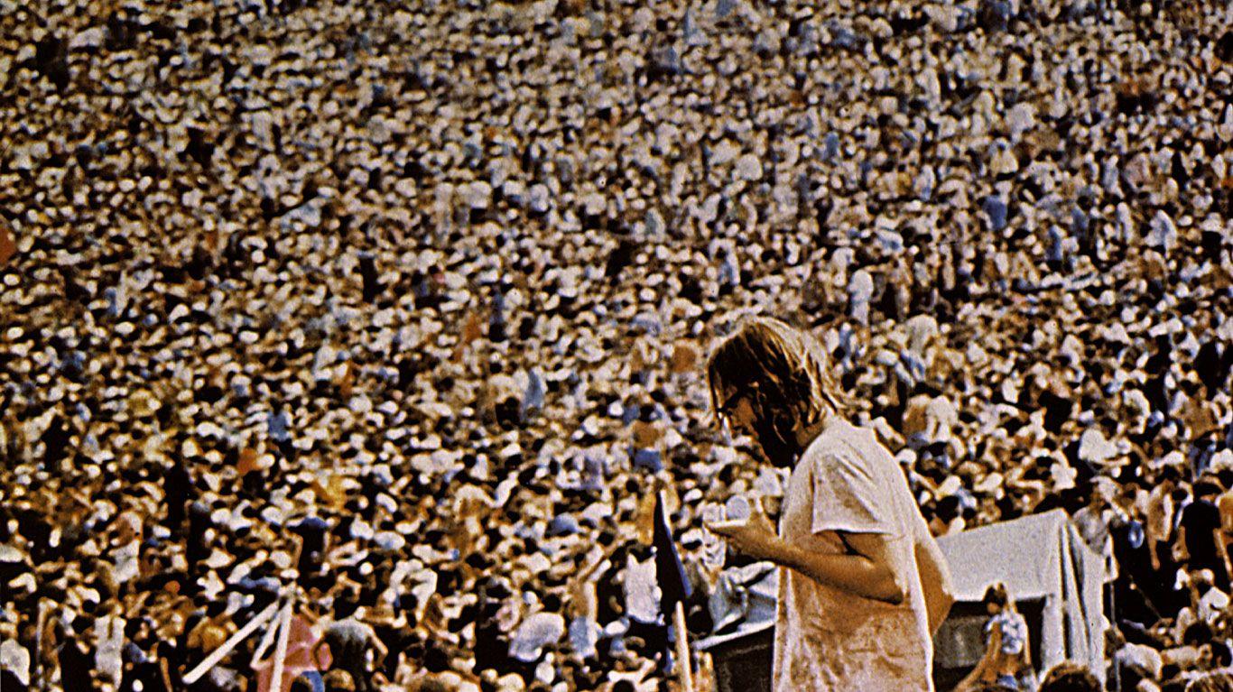 "An audience member against a sea of people in ""Woodstock."""